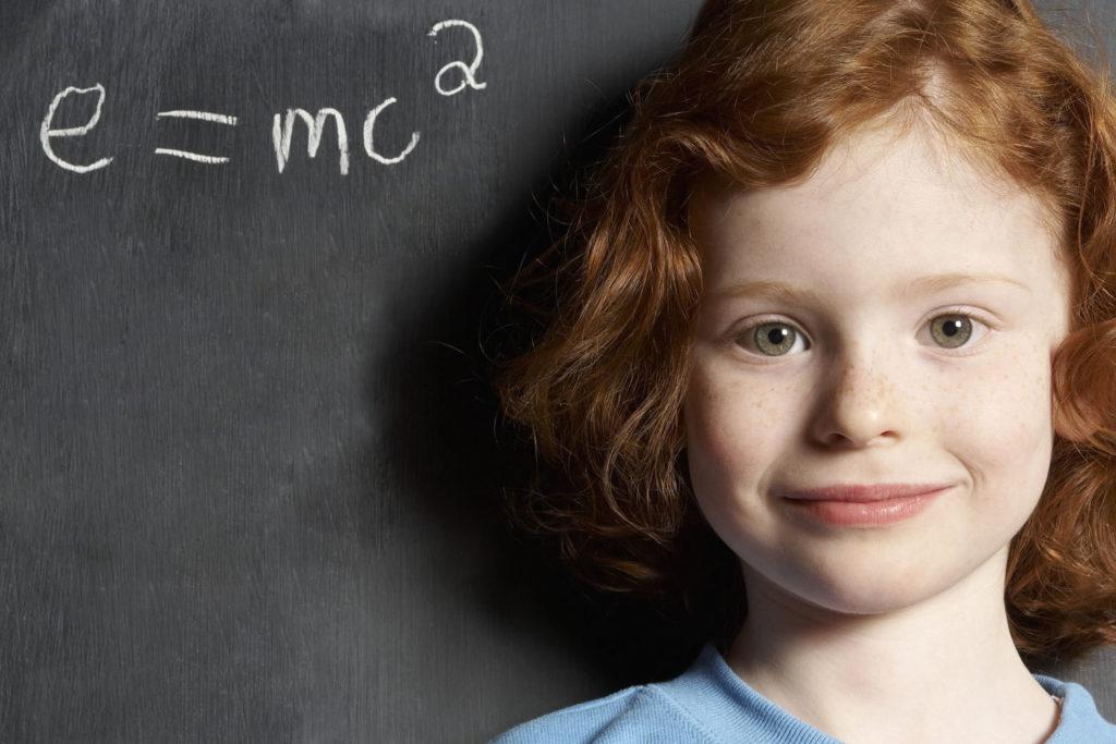 Girl (5-7) standing by formula on blackboard, smiling, portrait